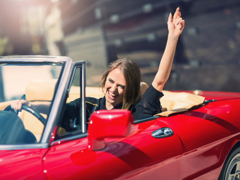 red convertible car with happy woman driving